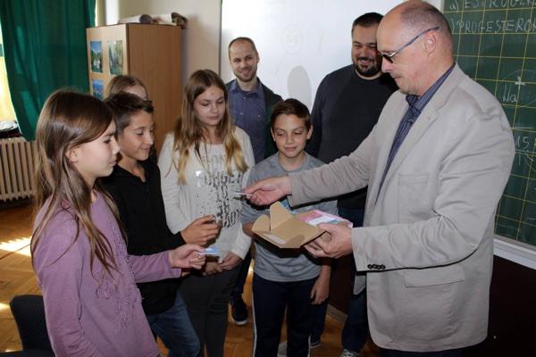 Na slici: Ravnatelj OŠ Milke Trnine Zlatko Hasan te Damir Dukarić i Mario Ivandić iz itSofta predaju memorijske uređaje učenicima.