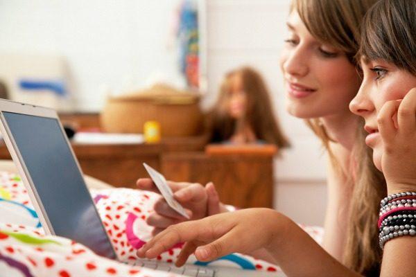 Girls Shopping on Laptop --- Image by © Mina Chapman/Corbis